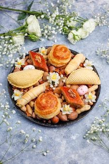 Traditional azerbaijan holiday novruz cookies baklavas and shakarburas on black tray plate on the grey concrete