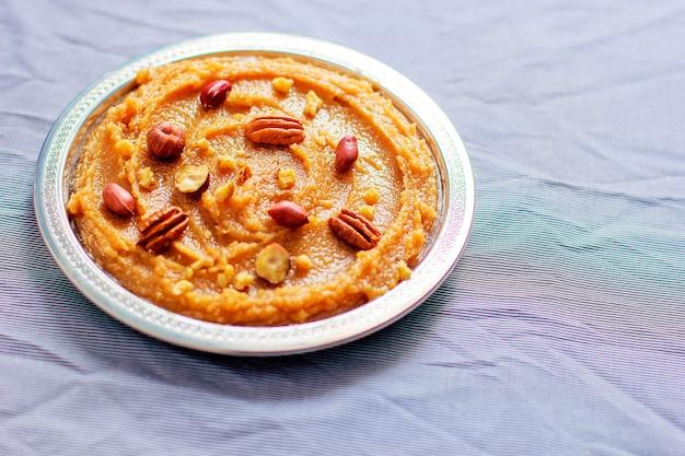 Традиционная азербайджанская, индийская, турецкая сладкая десертная халва с орехами на вершине