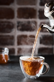 Traditional azerbaijani aromatic tea is poured into a cup