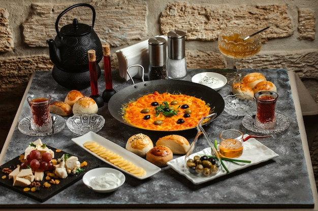 Traditional azerbaijani breakfast with egg and tomato dish, tea, cheese and butter