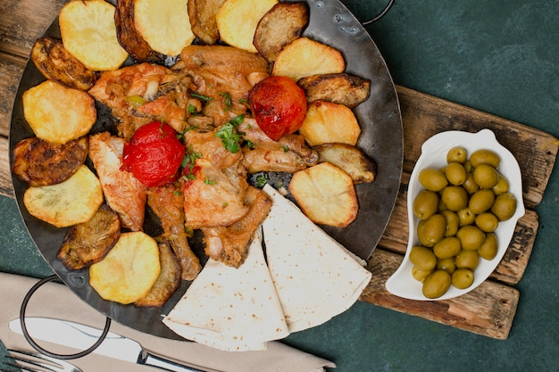Traditional azerbaijani dish with grilled meat and vegetables served with marinated olives