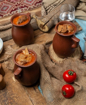 Traditional azerbaijani meal piti in pottery cups served with tomatoes.