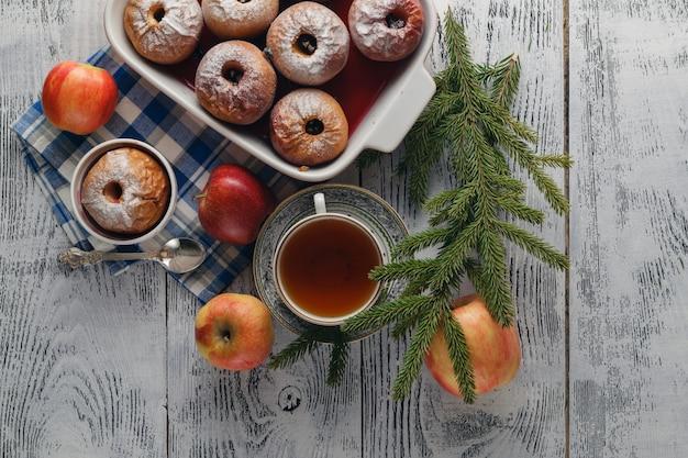 Традиционное запеченное яблоко на деревянном столе, с яблоком и сахарной пудрой. возле елки ветки и специи