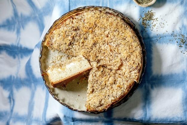 青と白のテーブルクロスで提供されるセラミック皿に玉ねぎ、ハーブ、チーズを添えた伝統的な焼きたてのパンケーキ