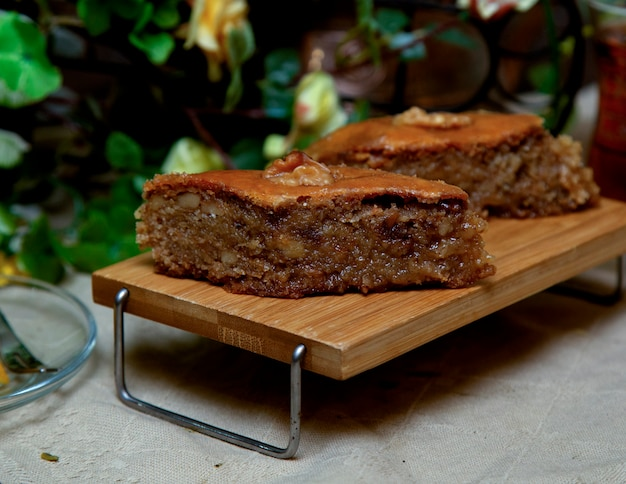 Traditional baklava on small wooden table with greenery