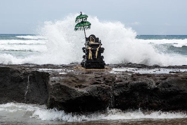 힌두교 우산과 바다 옆의 향기로운 막대기가있는 전통적인 발리 조각.