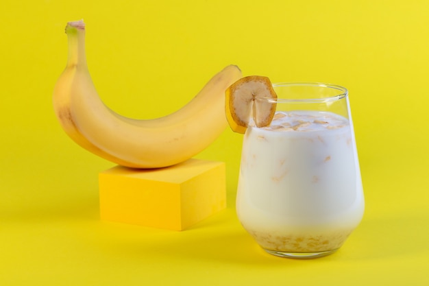 Traditional banana milk in a glass and ripe banana on yellow podium concept of a vegan alternative to traditional milk