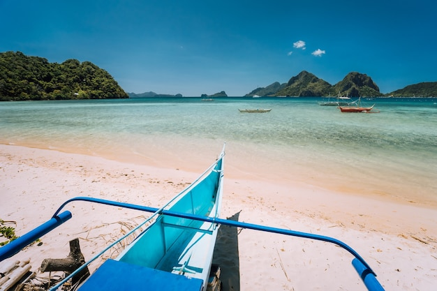 Traditional banca boat at the beach with blue lagoon and exotic nature scenery of el nido, palawan, philippines.