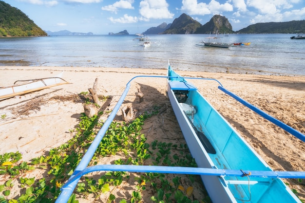 Traditional banca boat at sandy beach. shallow lagoon and coastline of el nido in background. palawan, philippines.