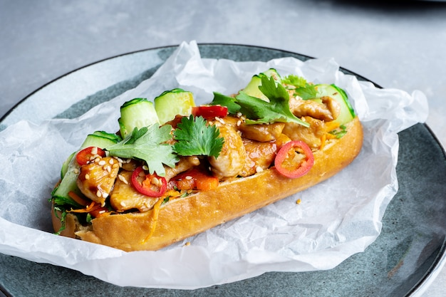 Traditional banh-mi sandwich with sweet and sour chicken, parsley, cucumber, chili pepper