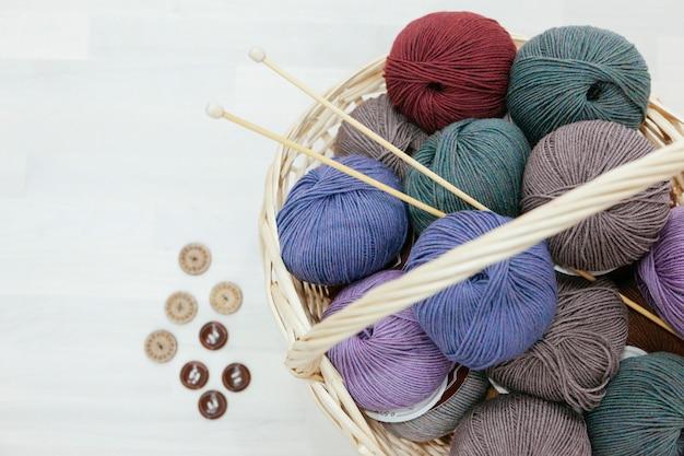 원사, 뜨개질 바늘 및 다양한 버튼의 다채로운 나무로 가득한 전통 바구니
