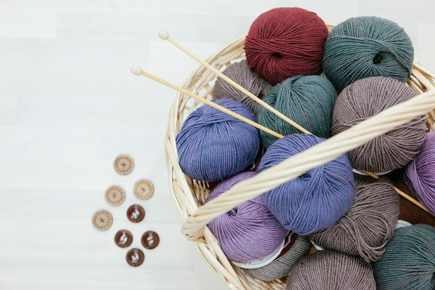 Traditional basket full with colorful wood of yarns, knitting needles and a variety of buttons