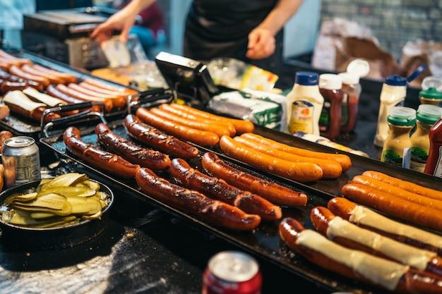 Традиционные барбекю барбекю колбаски на рождественской ярмарке в германии в европе в зимний период. german night street xmas и праздничная ярмарка в европейском городе.