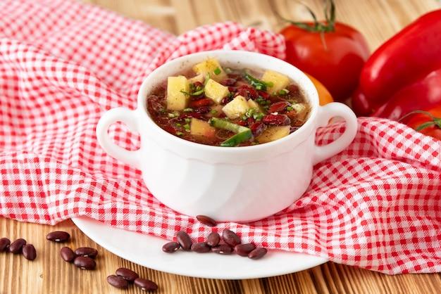Традиционный фасолевый суп с овощами и картофелем на деревянном фоне с чесноком.