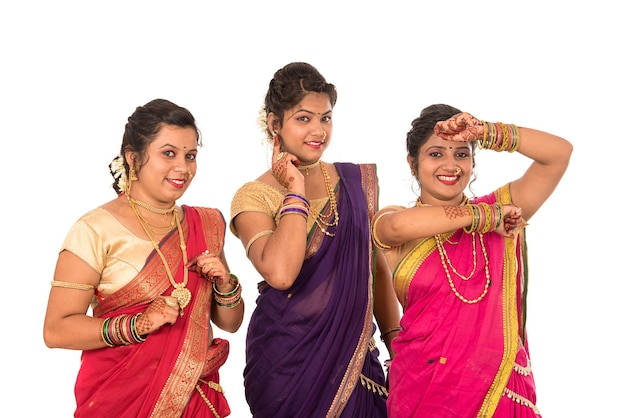 Traditional beautiful indian young girls in saree posing on white