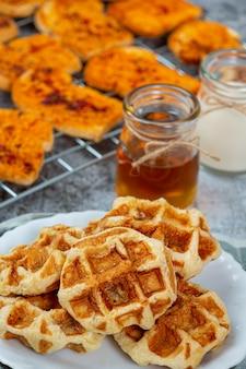 伝統的なベルギーワッフル、ブラッドオレンジ、ブルーベリーのドレッシング、甘い朝食のためのコーヒーカップ、明るい背景上の構成。