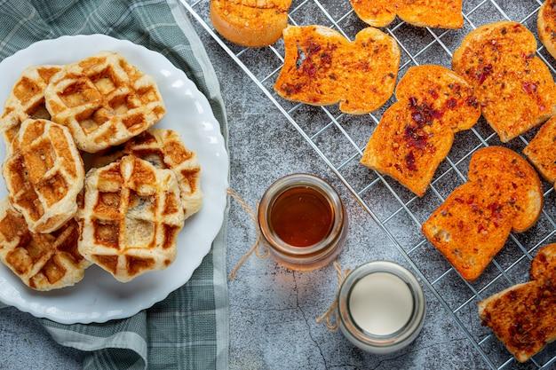 Традиционные бельгийские вафли, кровяные апельсины и ягоды черники и чашка кофе для сладкого завтрака, композиция на светлом фоне.