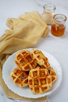 Cialde belghe tradizionali, arance rosse e salsa di mirtilli e tazza di caffè per colazione dolce, composizione su sfondo chiaro.