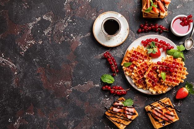 新鮮なベリーのフルーツとチョコレートソースとコーヒーを添えた伝統的なベルギーワッフル