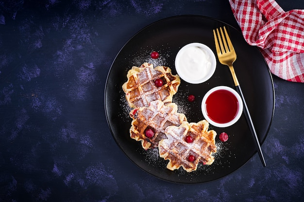 暗いテーブルにベリー、サワークリーム、ジャムを添えた伝統的なベルギーワッフル。上面図、オーバーヘッド
