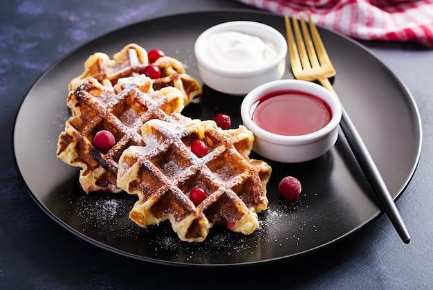 Cialde belghe tradizionali con frutti di bosco, panna acida e marmellata sul tavolo scuro.