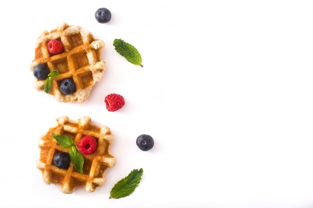 Traditional belgian waffles with blueberries and raspberries, isolated on white background