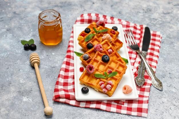 신선한 딸기와 회색 콘크리트 표면에 꿀 전통적인 벨기에 와플.
