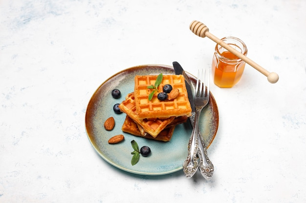 Traditional belgian waffles with fresh berries and honey on grey concrete surface.