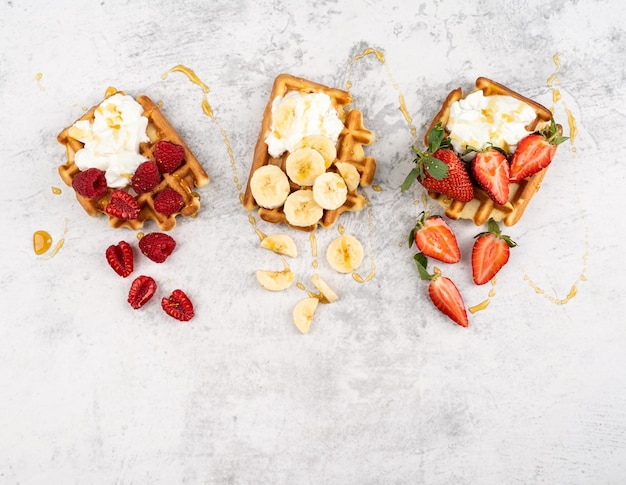 Traditional belgian waffles with fresh fruit and cream on white marble background. flat lay, top view, copy space.