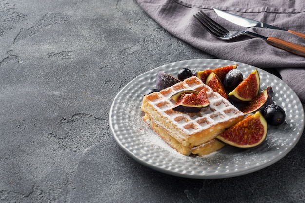 Traditional belgian waffles with powdered sugar grapes and figs.