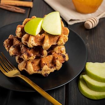 얇게 썬 녹색 사과와 꿀을 곁들인 전통적인 벨기에 와플은 어두운 나무 표면에 아침 식사 구성을 위해 제공됩니다.