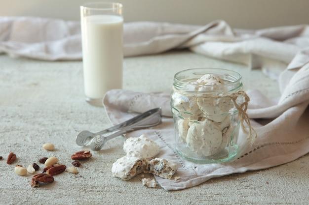 콘크리트 배경에 있는 유리병에 견과류를 넣은 전통적인 베즈 또는 머랭. 공간을 복사합니다. 우유 한 잔. 사랑으로 만든 수제 머랭.