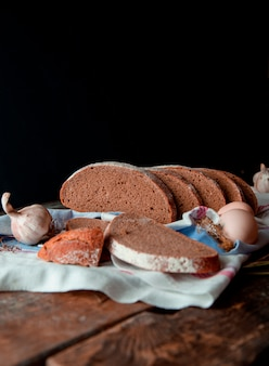 Traditional black bread side view thin slices with white flour on it, on a rustic towel  with garlic and eggs, on a wooden kitchen table.