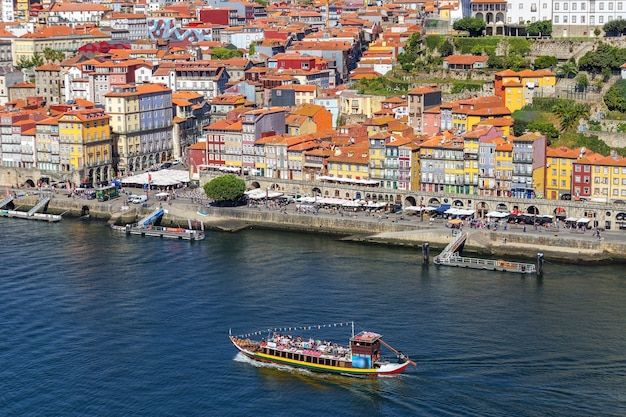 Traditional boats with barrels of wine, on the douro river in the portuguese city of porto.