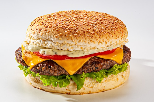 Traditional brazilian cheeseburger, with bread, melted cheese, lettuce, tomato, mayonnaise on white background.