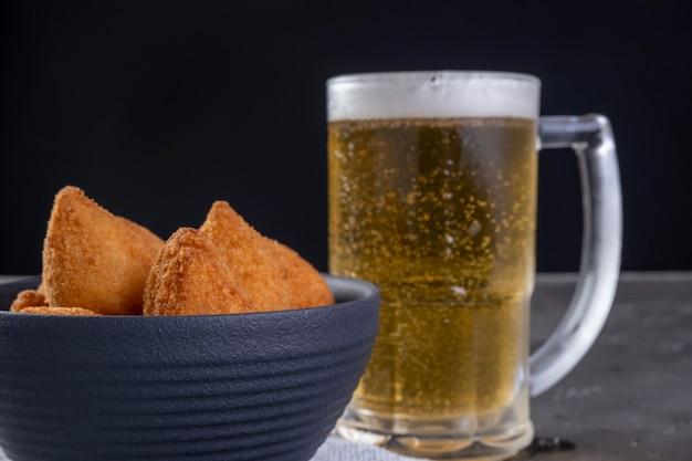 닭고기와 맥주 한 잔으로 채워진 전통적인 브라질 튀김 간식. coxinha.