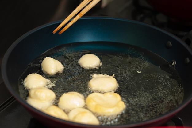 Bolinho de chuva라는 브라질 전통 수제 과자를 프라이팬에 튀겨내고 있습니다.