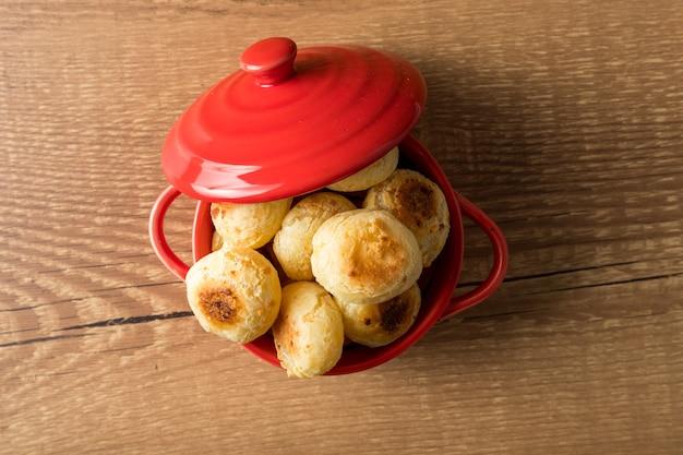 Традиционный бразильский закусочный сырный хлеб в деревенской красной кастрюле