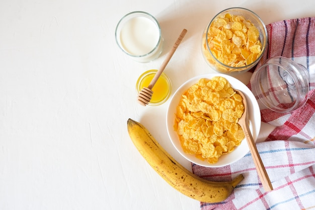 Traditional breakfast cereal of cornflakes and milk with a banana