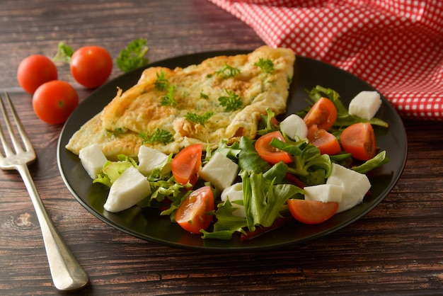 Traditional breakfast - egg omelette with cherry tomato, mozzarella and green salad. .