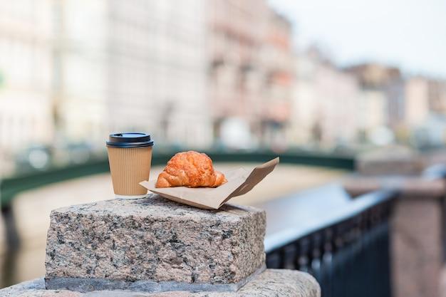 屋外のコーヒーと焼きたてのクロワッサンの伝統的な朝食