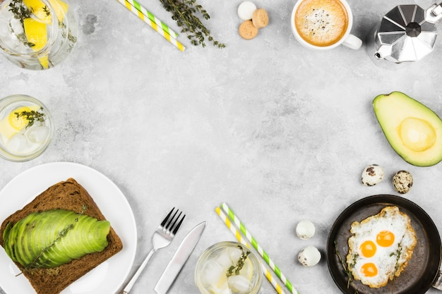 Traditional breakfast - toast from rye bread with avocado, fried eggs from quail eggs, coffee, lemonade on a light background. top view, copy space. food background.