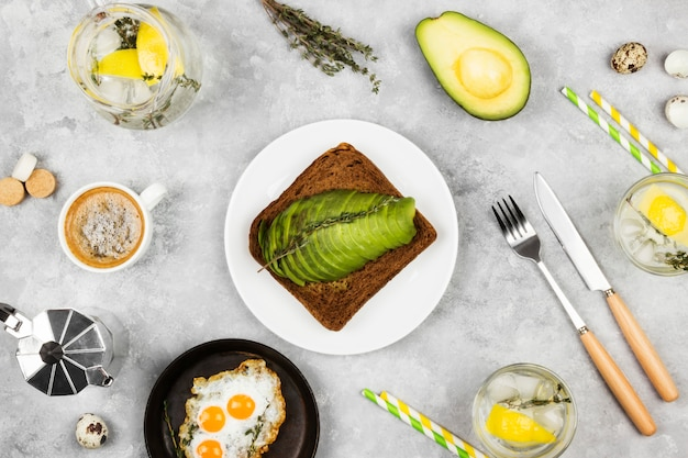Traditional breakfast - toast from rye bread with avocado, fried eggs from quail eggs