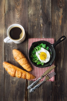 Traditional breakfast with coffee, croissants and fried egg in iron skillet on rustic wooden.