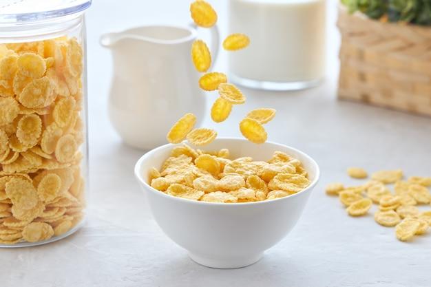 흰색 테이블에 우유와 함께 그릇에 떨어지는 콘플레이크와 함께 전통적인 아침 식사 프리미엄 사진