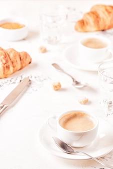 Традиционный завтрак со свежими круассанами на белой поверхности, вертикаль.