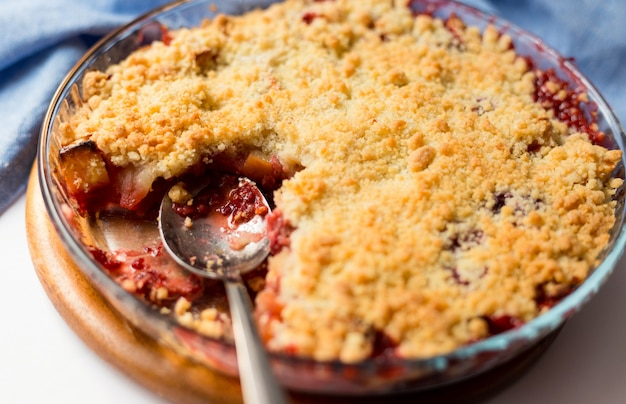 Traditional british red berry crumble in glass baking dish with cloth. close up. delicious dessert in rustic style, selective focus