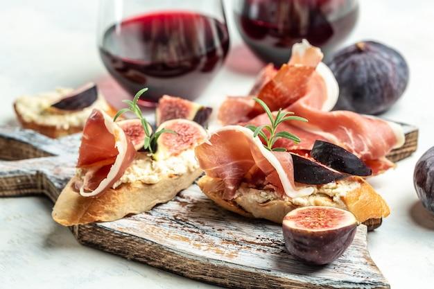 파르마 말린 햄과 프로슈토를 곁들인 전통 브루스케타 세트. 전채. 전채, 스낵 및 와인.