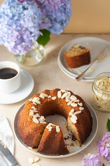 Traditional bundt cake, homemade pastry baked round cake with coffee cup and flowers on background