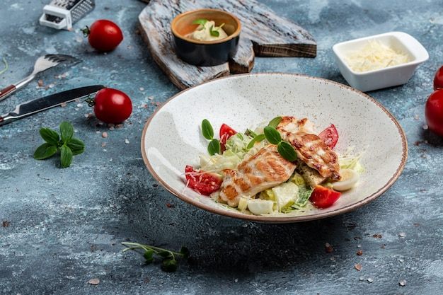 Traditional caesar salad in bowl with grilled chicken, leaves, sauce and parmesan. restaurant menu, dieting, cookbook recipe. top view.
